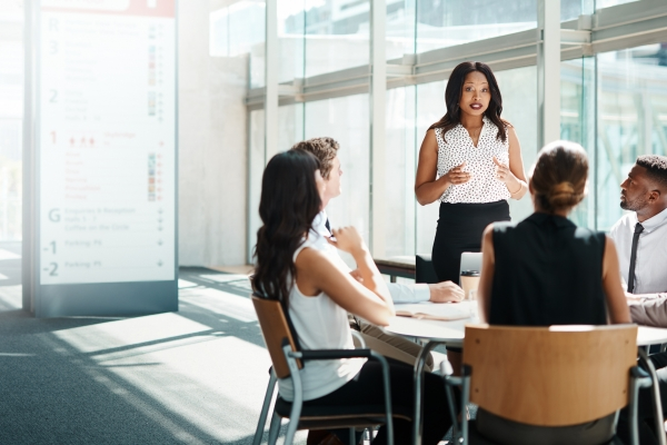 Businesswoman leading a meeting in a glass office